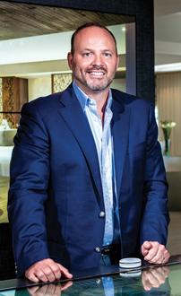 A man in a dark blue suit, Mark R. Blackburn, President of Marquis Management